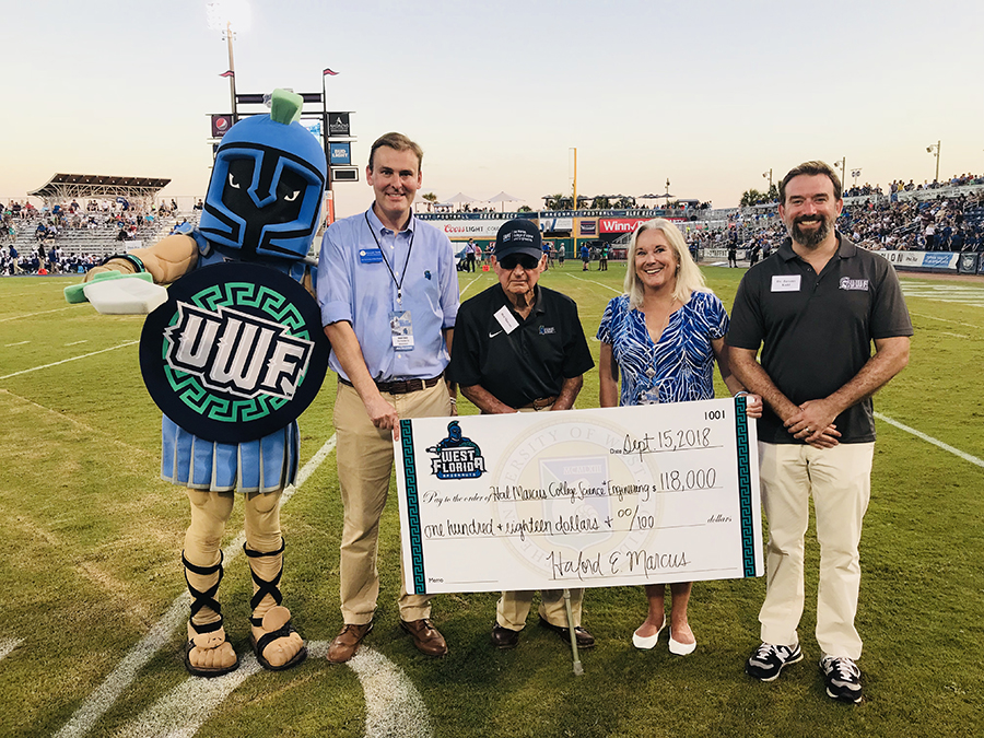 Howard Reddy, VP of University Advancement, Marcus, Saunders and Kuhl pose with a check at Wahoos Field on Sept. 15, 2018