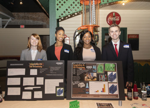 A group of four UWF College of Business Supply Chain Logistics Management students standing behind their projects created in the Sea3D lab.