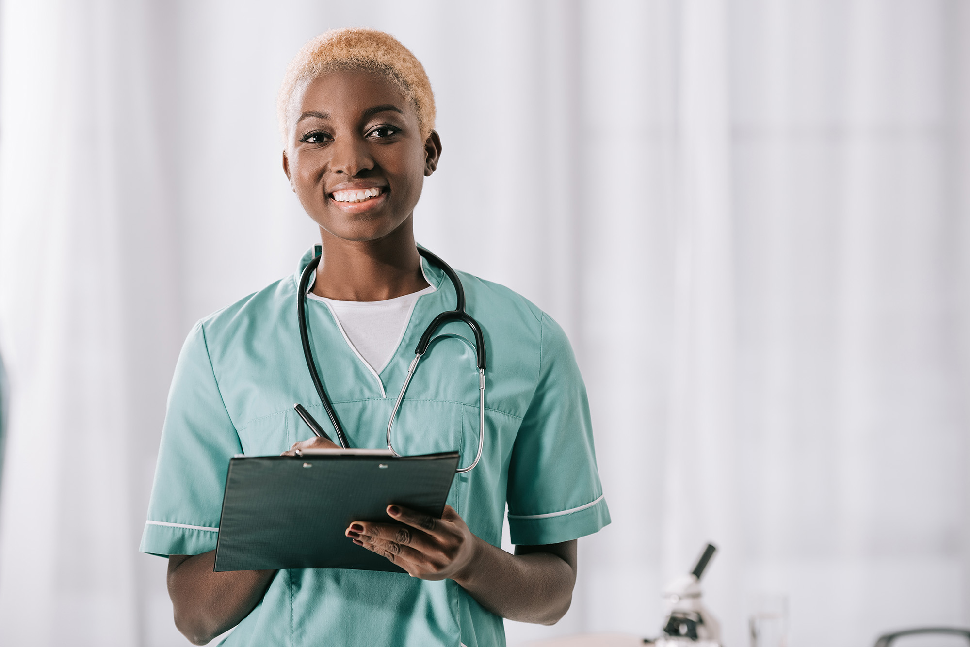 smiling african american woman with stethoscope and clipboard