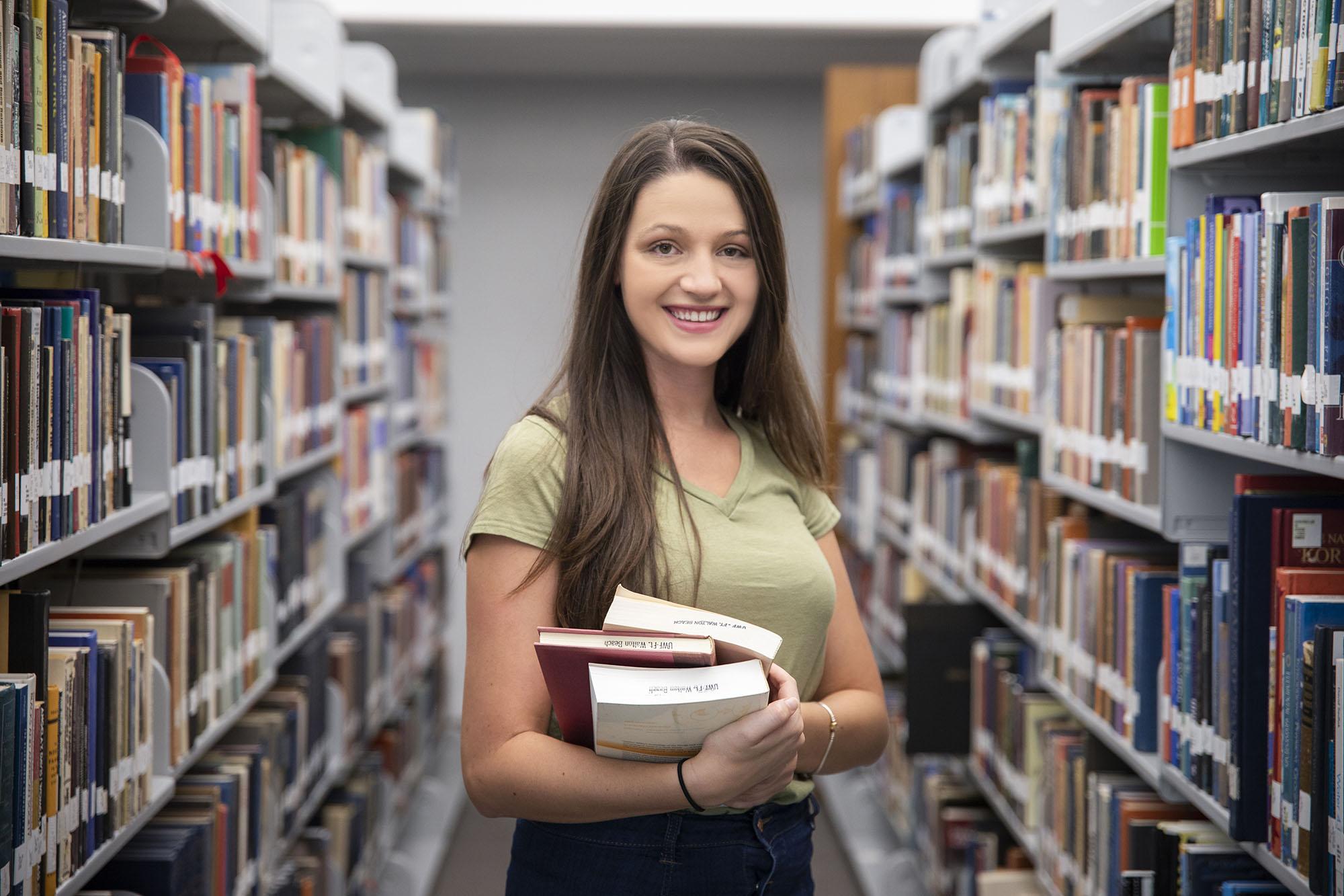 UWF student holding books in the UWF Emerald Coast Library