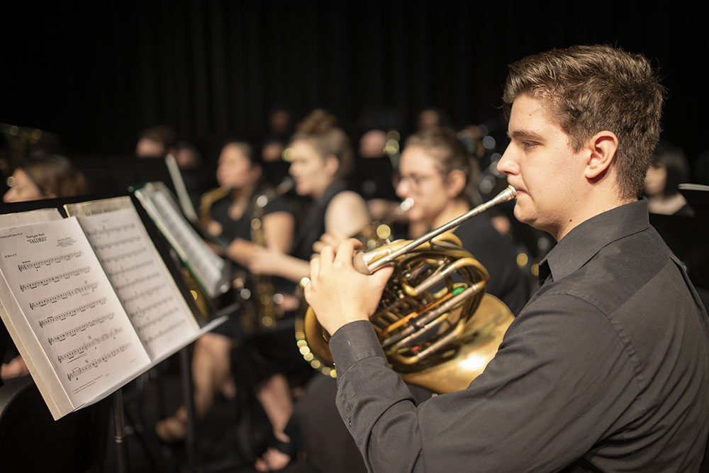 The UWF Symphonic Band music ensemble performing on the Mainstage Theatre in the Center for Fine and Performing Arts