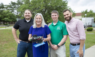 UWF President Martha Saunders poses with the university's Robotics Team and their prize-winning creation on the Cannon Green.