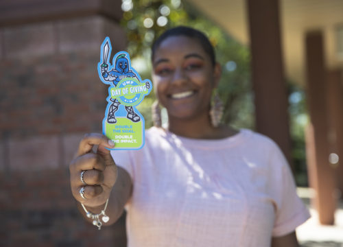 UWF student holds Argie cut-out in honor of Day of Giving during UWF Founders Week