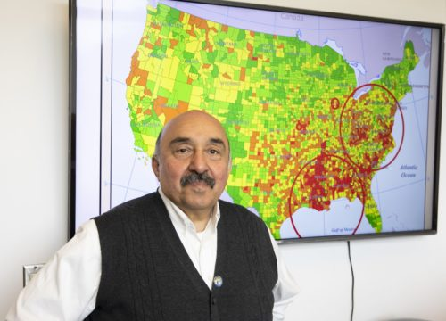 Dr. Raid Amin, a distinguished university professor in the Department of Mathematics and Statistics, stands before a map where his research has identified high rates of breast cancer death in America.
