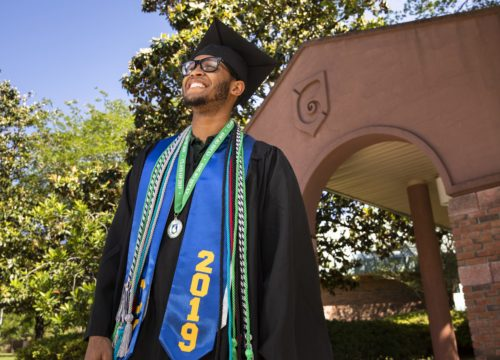 UWF graduate poses in front of the archway on the Pensacola campus.