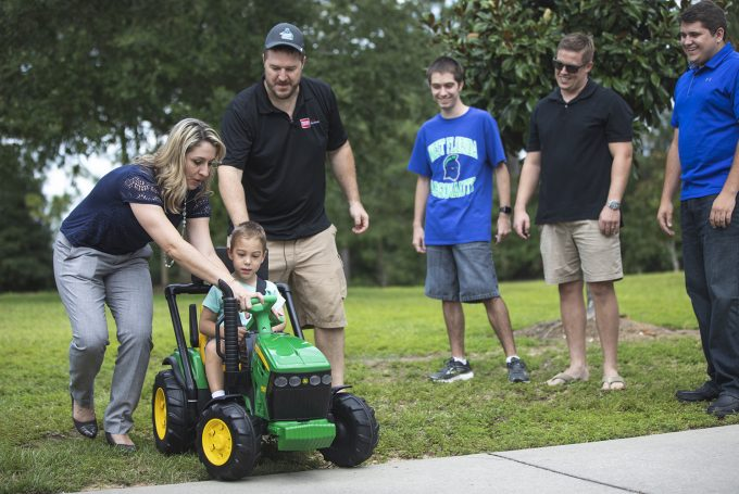 Four-year-old Jack Carroll receives the first modified vehicle from UWF's ArgoTots program