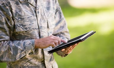 Mid-section of soldier using digital tablet in park on a sunny day