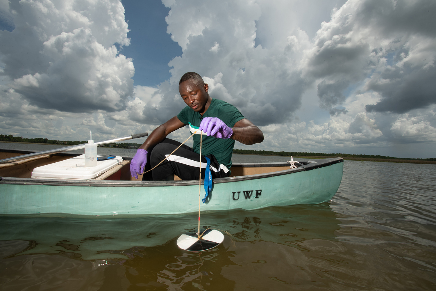 Jani Ngalame collects water samples in Indian Bayou Friday July 19, 2019 in Milton Florida.