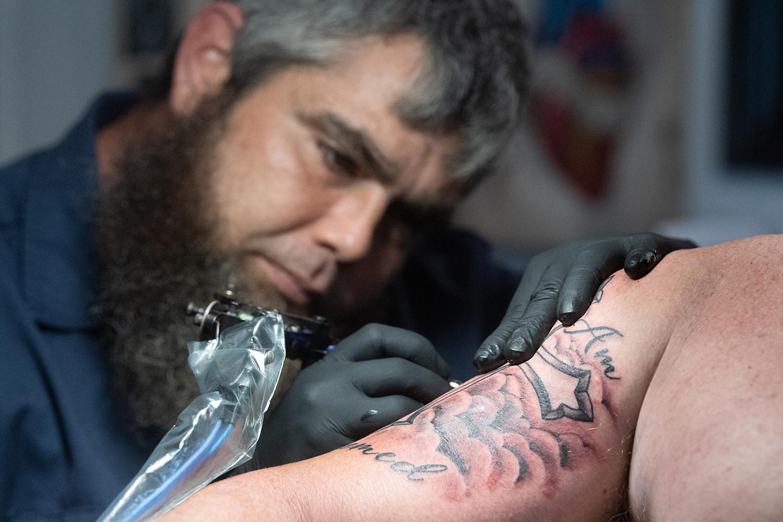 "Shane ""Big Jolly"" gives a tattoo to Brandon Gallups at Gulf Coast Tattoos"