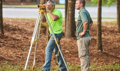 Dr. Nye Grant's class practices surveying techniques on the University of West Florida's main campus.