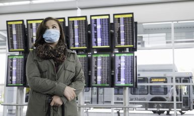 A cautious female traveler at the airport wearing a mask to protect herself from disease, possibly fearful of Ebola.