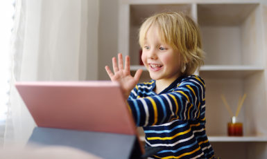 Little boy is meeting and talking in video chat. Stay at home during quarantine.Communication with relatives and friends online. Keeping social distance.