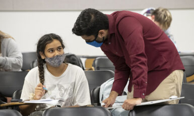 instructor watching over the shoulder of a student at a desk