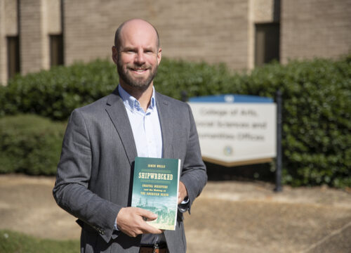 Dr. Jamin Wells, assistant professor and director of the Public History Master's Program, poses with his recent book, Shipwrecked: Coastal Disasters and the Making of the American Beach, at the College of Arts, Social Sciences and Humanities offices on Nov. 24, 2020.