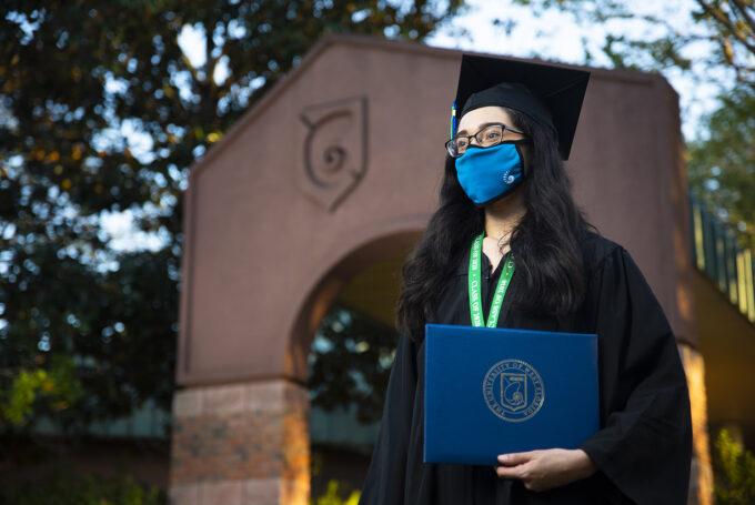 UWF students pose in their graduation regalia at the Pensacola campus on Nov. 20, 2020.