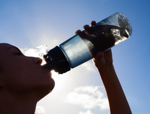 Female drinking a bottle of water. Stock photo.