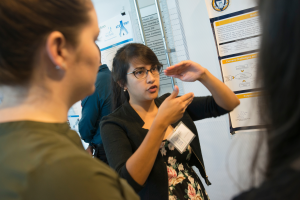 Amanda Tonnaer talks about her research project during the Summer Undergraduate Research Program Symposium poster session at the University of West Florida.