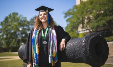 UWF students pose in their graduation regalia on the Pensacola campus on Apr. 21, 2021.